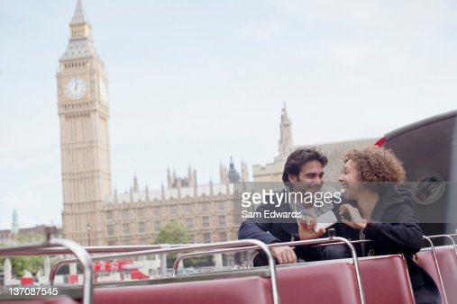 Couple with digital camera riding double decker bus near Big Ben clocktower in London : Stock Photo