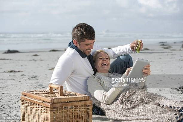 Couple with digital tablet having picnic on a beach
