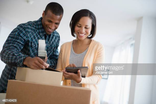 Couple with digital tablet taping up moving boxes
