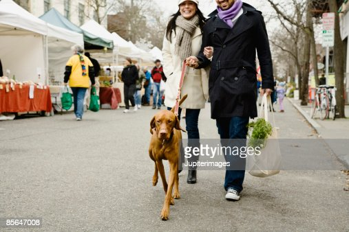 Couple with dog at farmer's market : Stock Photo