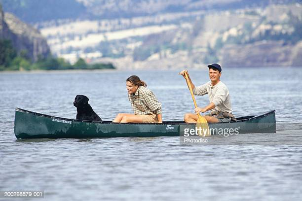 Couple with dog canoeing on lake