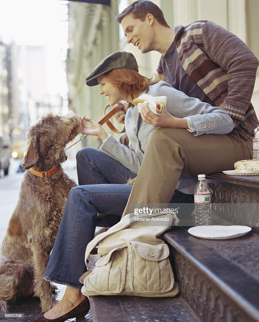 Couple with Dog Enjoying Hot Dogs : Photo