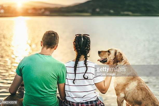 Couple with dog enjoying summer sunset