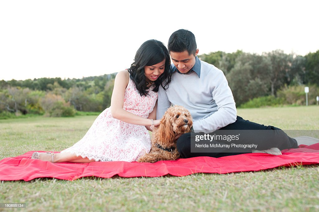 Couple with dog on picnic blanket : Stock Photo
