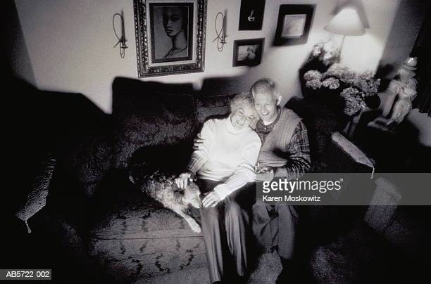 Couple with dog on sofa watching television (B&W)