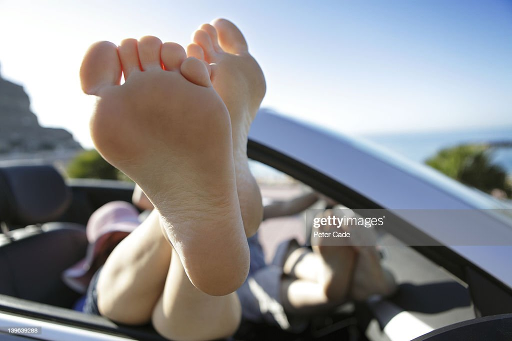 couple with feet up, relaxing in car by sea : Stock Photo