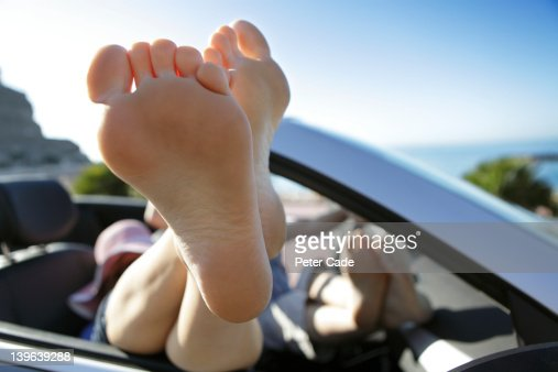 couple with feet up, relaxing in car by sea