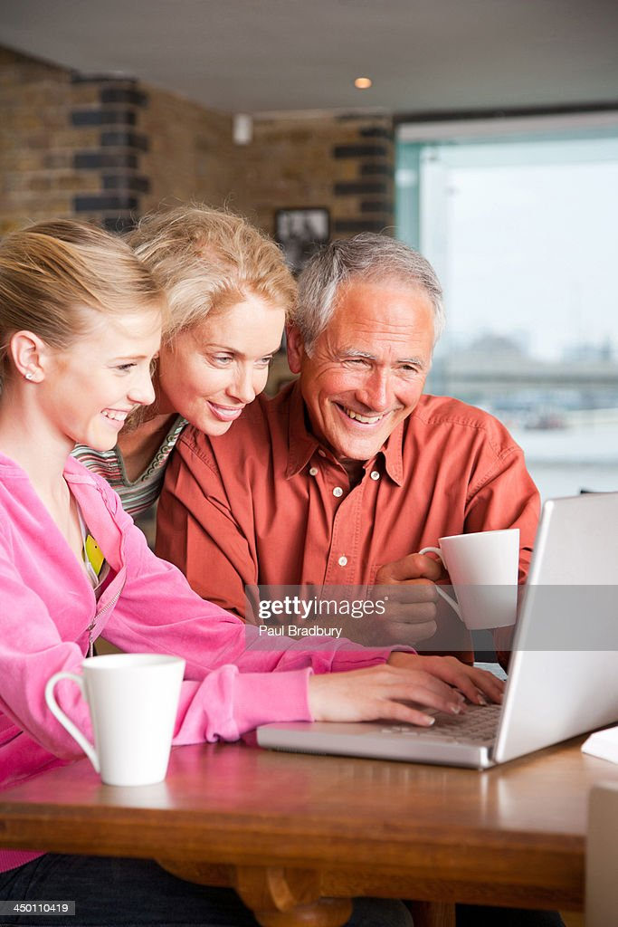 Couple with girl on laptop in modern home : Stock Photo