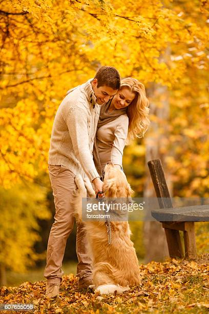 Couple with golden retriever in park