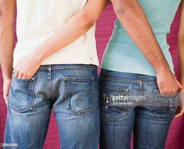 Couple with hands in each other's rear jeans pockets