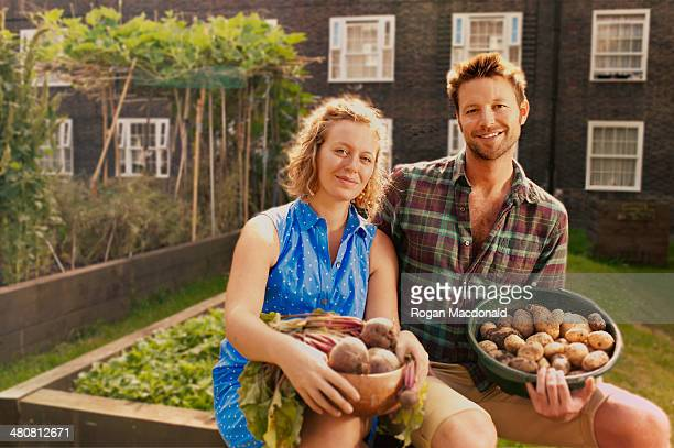 Couple with harvested potatoes and beets on council estate allotment