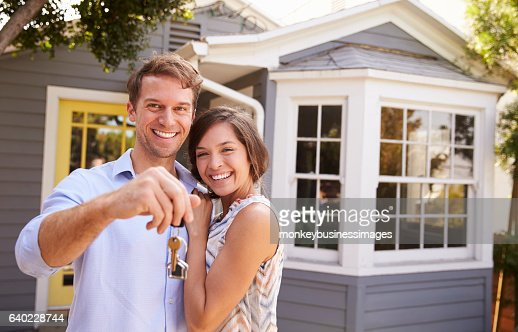 Couple With Keys Standing Outside New Home : Stock Photo