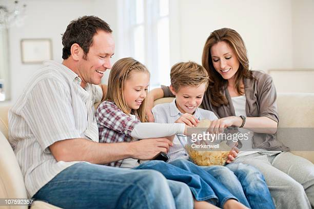 Couple with kids (8-11) having chips at home