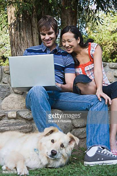 Couple with laptop computer and dog