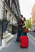 Couple with luggage on London street, England