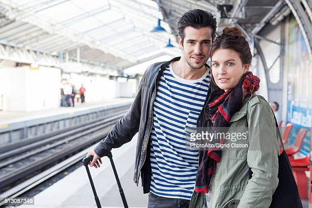 Couple with luggage on train platform