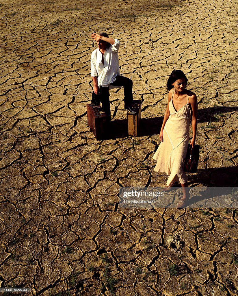 Couple with luggage standing on cracked mud surface : Stock Photo