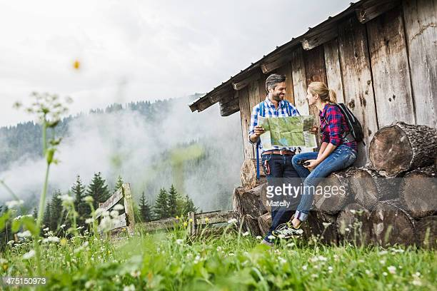 Couple with map discussing their trek, Tirol, Austria