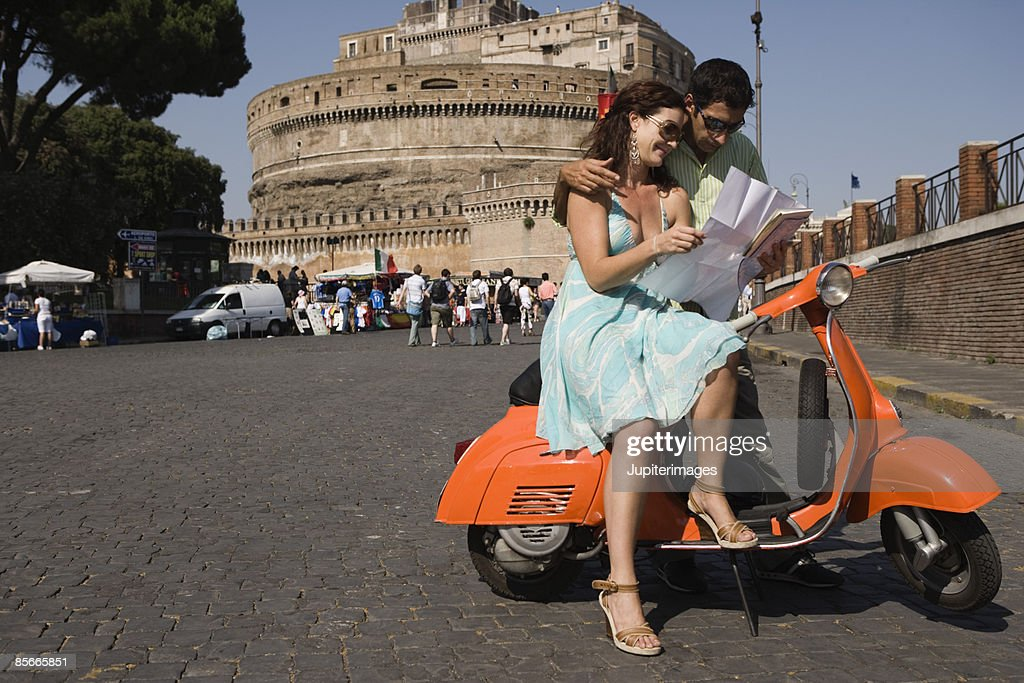 Couple with map on motor scooter , Saint Angel Castle , Rome , Italy