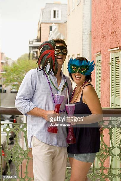 Couple with masquerade masks on balcony with drinks