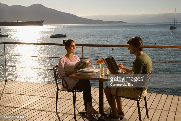 Couple with menus at table on deck overlooking sea, sunset