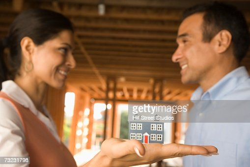Couple with model house inside construction site : Stock Photo