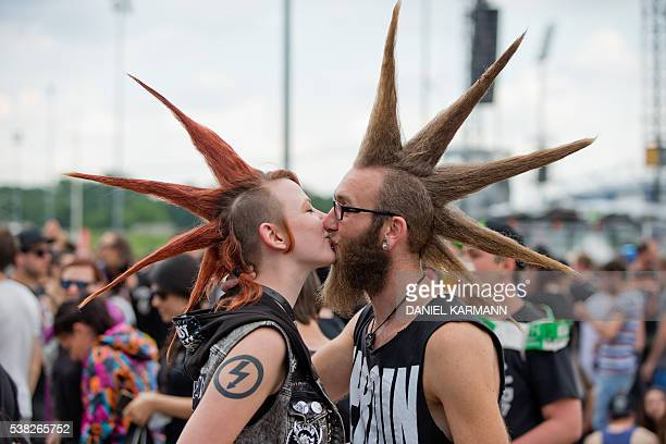 A couple with mohican styled hair kiss on June 5 2016 at the Rock im Park music festival in Nuernberg / AFP / dpa / Daniel Karmann / Germany OUT