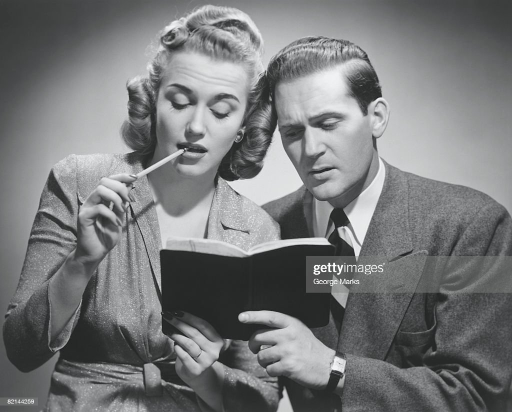 Couple with opened folder and pencil in studio, (B&W) : Stock Photo