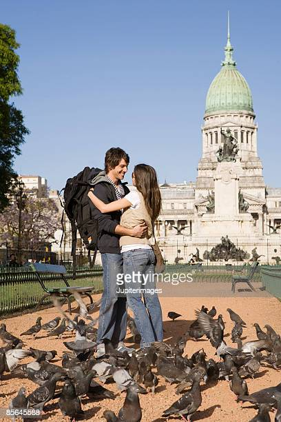 Couple with pigeons in front of monument