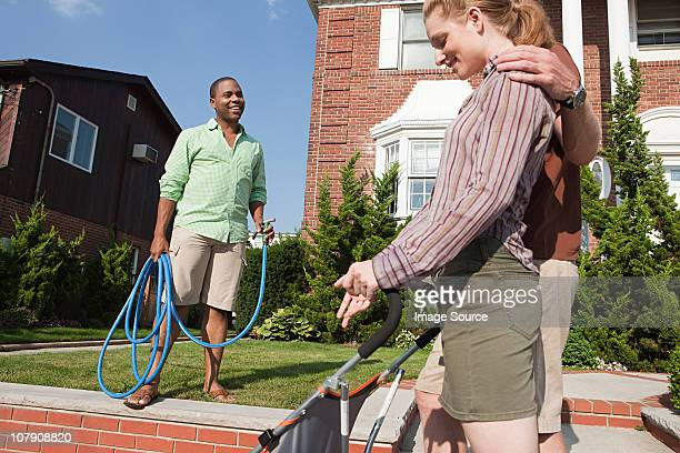 Couple with pushchair talking to neighbor