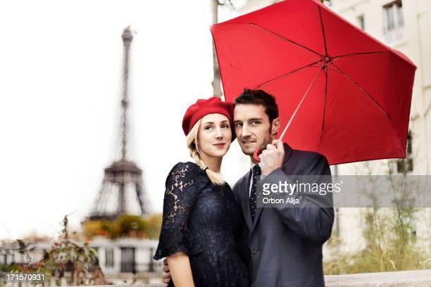 Couple avec parapluie rouge à proximité de la Tour Eiffel