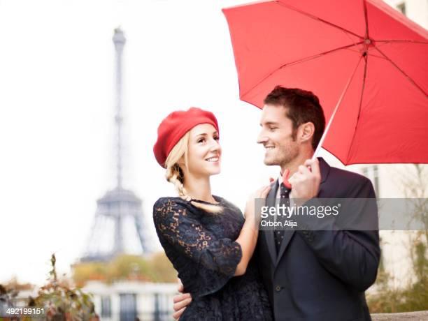 Coppia con ombrello rosso vicino alla Torre Eiffel