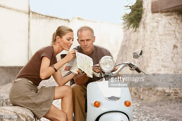 Couple With Scooter Reading Map