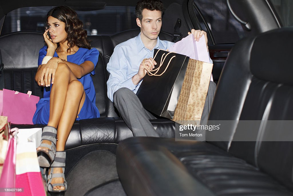 Couple with shopping bags in backseat of limo : Stock Photo