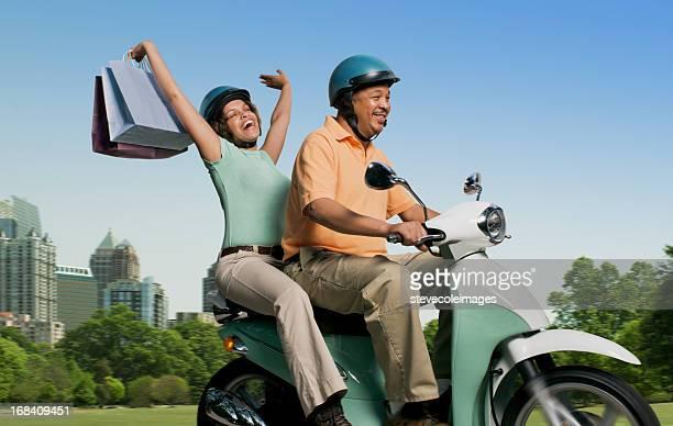 Paar mit Einkaufstaschen Reiten Roller
