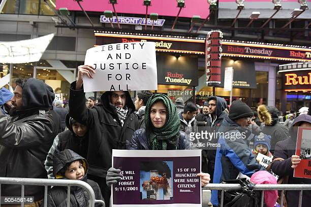 Couple with signs calling on UN intervention Hundreds of Muslims gathered in Times Square to protest against the Saudi government's execution of...