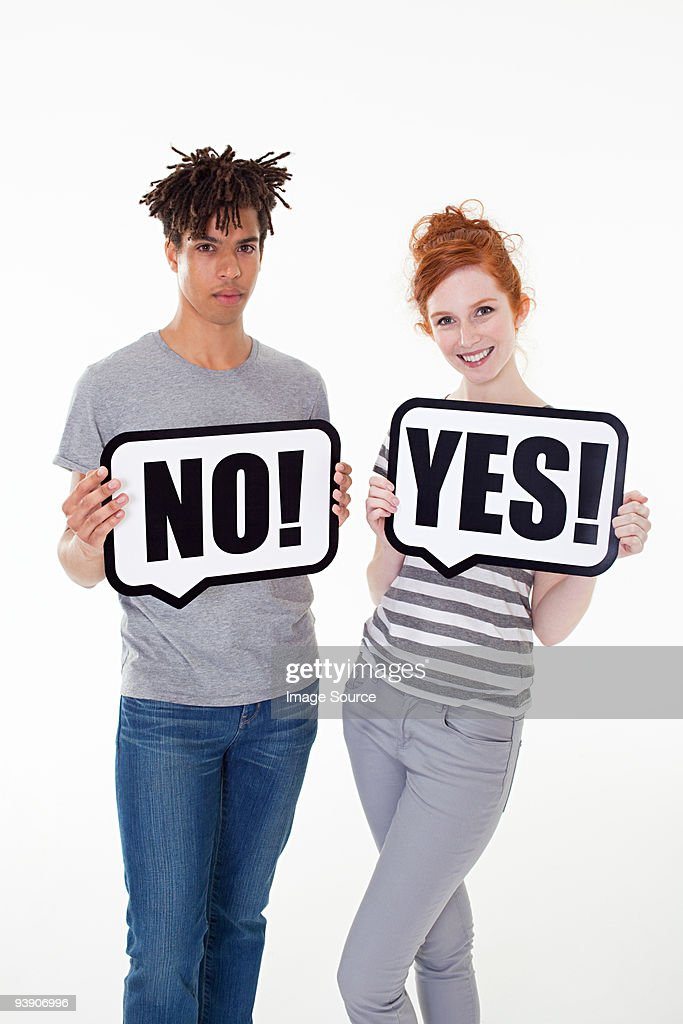 Couple with signs that read no and yes : Stock Photo