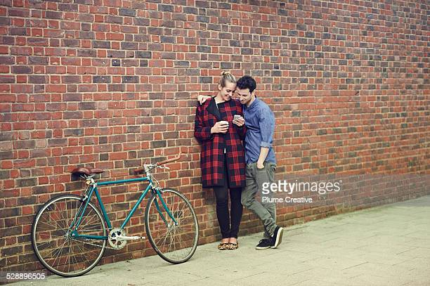 Couple with smartphone and bike