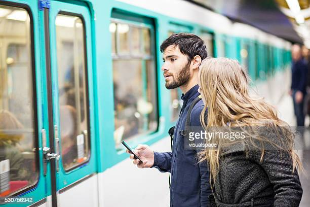 Couple With Smartphone Travelling By Subway