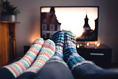 Couple with socks and woolen stockings watching movies or series on tv in winter. Woman and man sitting or lying together on sofa couch in home living room using online streaming service in television