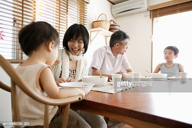Couple with son (8-9 years) and baby boy (18-24 months) eating at dining table