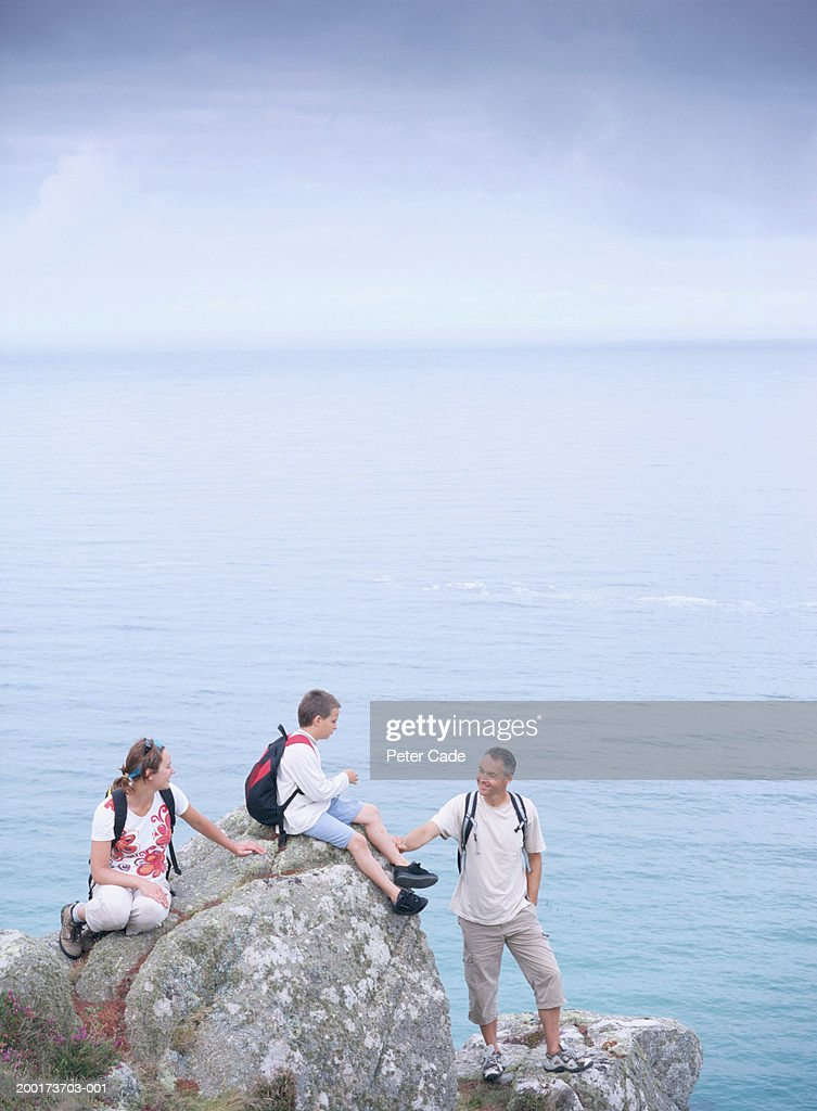 Couple with son (10-12) on rocks by ocean : Stock Photo