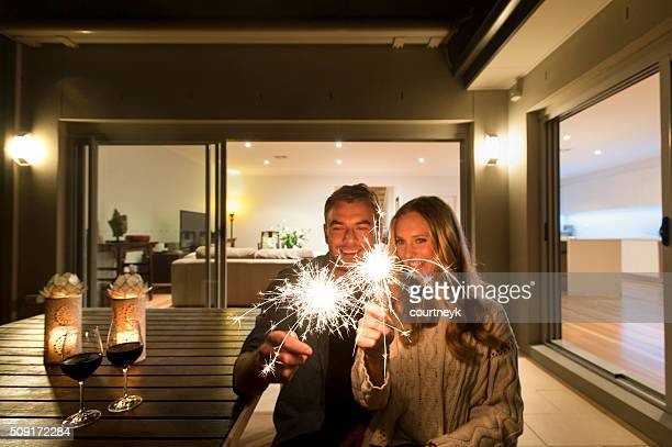 Couple with sparklers outside their home at night.