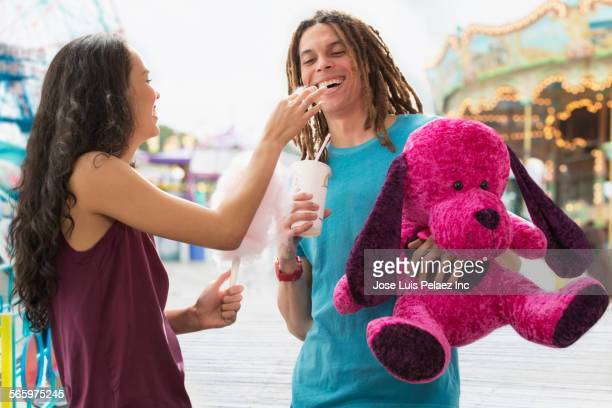 Couple with stuffed animal and cotton candy at amusement park