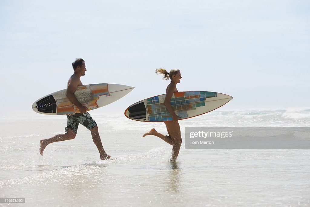 Couple with surfboards running on beach : Stock Photo