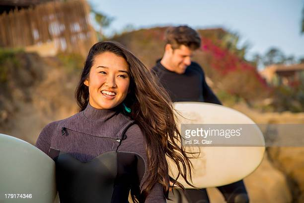 Couple with surfboards walking on cliffs to ocean