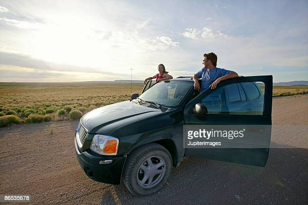 Couple with SUV on desert road