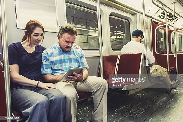Couple with Tablet on Subway