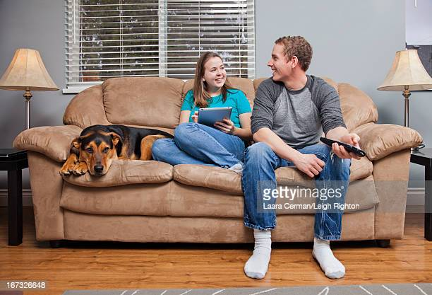 Couple with their dog relaxing at home.