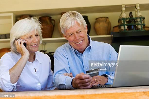 Couple avec leur téléphone portable et ordinateur portable à la recherche